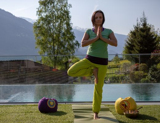 "[Translate to en:] Yoga-Trainerin Carola macht die Yoga-Übung ""Baum"" am Sole-Pool im Gartenhotel Crystal"